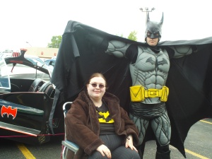 Kat Fury and Batman infront of the 1960s Batmobile. Batman has his cape stretched out behind both people.